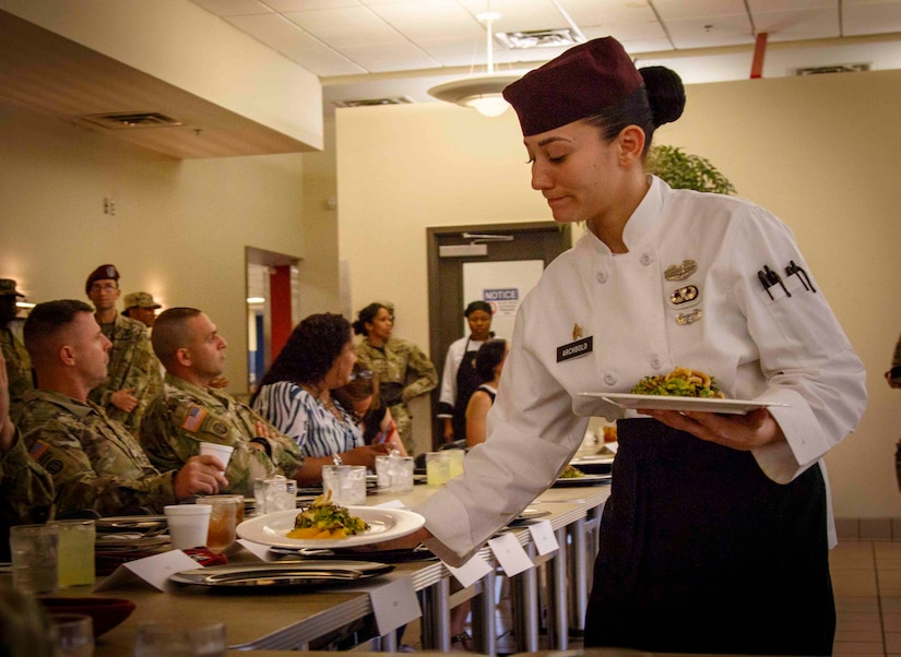 Military chef serves a course during a competition.