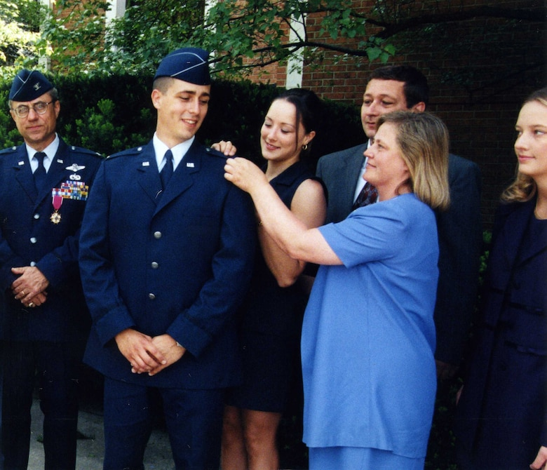 Col. Richard Evans, West Virginia University aerospace science professor and Detachment 915 commander, looks on as 2nd Lt. Dan Cooley, WVU ROTC graduate, gets a gold bar pinned on by his wife, Terese, his father, Chuck, his mother, LouAnn, and his sister, Beth, during his promotion ceremony May 15, 1999.