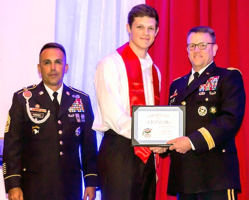 "Army Brig. Gen. Bill Boruff, commander of the Mission and Installation Contracting Command, and Command Sgt. Maj. Marco Torrez pose with a future Soldier, who was honored during ""A Night in Your Honor"" hosted by Our Community Salutes-San Antonio held in the Rosenberg Sky Room at the University of the Incarnate Word May 16.  Each honoree received an OCS certificate and challenge coin."