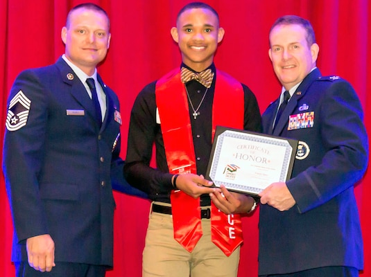 "Air Force Col. Sean McKenna, chief of Plans and Resources Division, Headquarters Air Force Recruiting Service, and Chief Master Sgt. William Rawls pose with a future Airman, who was honored during ""A Night in Your Honor"" hosted by Our Community Salutes-San Antonio held in the Rosenberg Sky Room at the University of the Incarnate Word May 16."