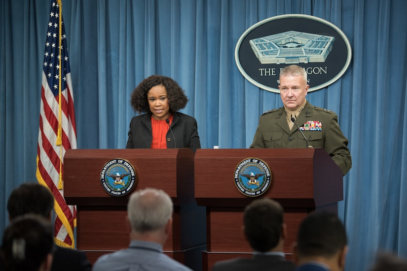 A man and a woman stand at podiums at the Pentagon.