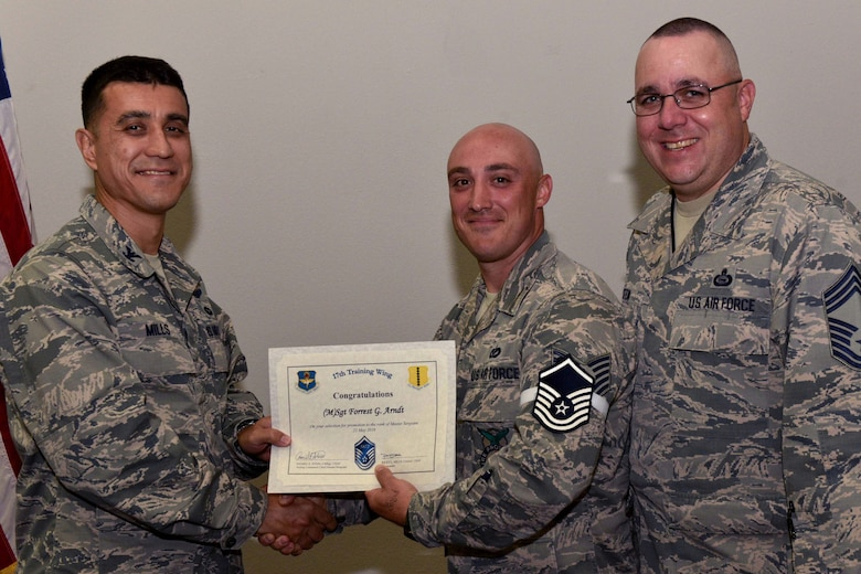 U.S. Air Force Col. Ricky Mills, 17th Training Wing commander, presents Tech. Sgt. Forrest Arndt, 312th Training Squadron instructor, their certificate of selection with Chief Master Sgt. Daniel Stein, 17th TRW command chief, during a Master Sergeant release party at the Event Center on Goodfellow Air Force Base, Texas, May 25, 2018. Goodfellow held the party to notify the selected promotees and to give fellow wingmen and friends an opportunity to congratulate them on their success. (U.S. Air Force photo by Senior Airman Randall Moose)