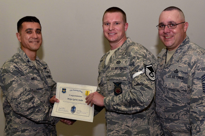 U.S. Air Force Col. Ricky Mills, 17th Training Wing commander, presents Tech. Sgt. Kyle Dobler, 312th Training Squadron instructor, their certificate of selection with Chief Master Sgt. Daniel Stein, 17th TRW command chief, during a Master Sergeant release party at the Event Center on Goodfellow Air Force Base, Texas, May 25, 2018. Goodfellow held the party to notify the selected promotees and to give fellow wingmen and friends an opportunity to congratulate them on their success. (U.S. Air Force photo by Senior Airman Randall Moose)