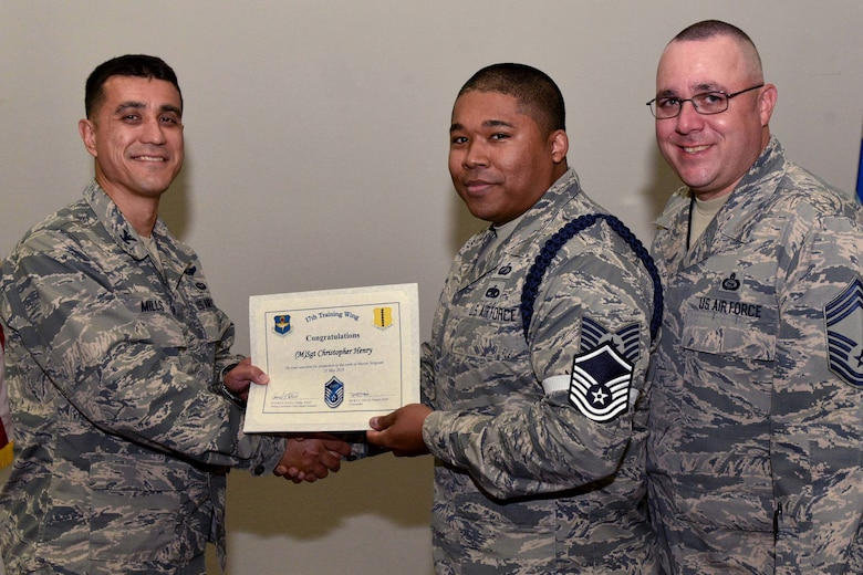 U.S. Air Force Col. Ricky Mills, 17th Training Wing commander, presents Tech. Sgt. Christopher Henry, 316th Training Squadron instructor, their certificate of selection with Chief Master Sgt. Daniel Stein, 17th TRW command chief, during a Master Sergeant release party at the Event Center on Goodfellow Air Force Base, Texas, May 25, 2018. Goodfellow held the party to notify the selected promotees and to give fellow wingmen and friends an opportunity to congratulate them on their success. (U.S. Air Force photo by Senior Airman Randall Moose)
