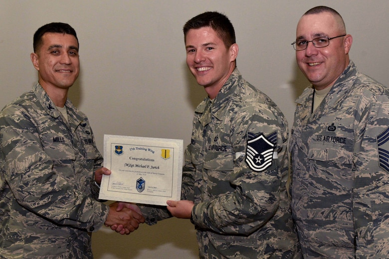 U.S. Air Force Col. Ricky Mills, 17th Training Wing commander, presents Tech. Sgt. Michael Jurich, 315th Training Squadron instructor, their certificate of selection with Chief Master Sgt. Daniel Stein, 17th TRW command chief, during a Master Sergeant release party at the Event Center on Goodfellow Air Force Base, Texas, May 25, 2018. Goodfellow held the party to notify the selected promotees and to give fellow wingmen and friends an opportunity to congratulate them on their success. (U.S. Air Force photo by Senior Airman Randall Moose)