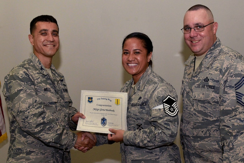 U.S. Air Force Col. Ricky Mills, 17th Training Wing commander, presents Tech. Sgt. Gloria Westbrooks, 17th Mission Support Group executive assistant, their certificate of selection with Chief Master Sgt. Daniel Stein, 17th TRW command chief, during a Master Sergeant release party at the Event Center on Goodfellow Air Force Base, Texas, May 25, 2018. Goodfellow held the party to notify the selected promotees and to give fellow wingmen and friends an opportunity to congratulate them on their success. (U.S. Air Force photo by Senior Airman Randall Moose)