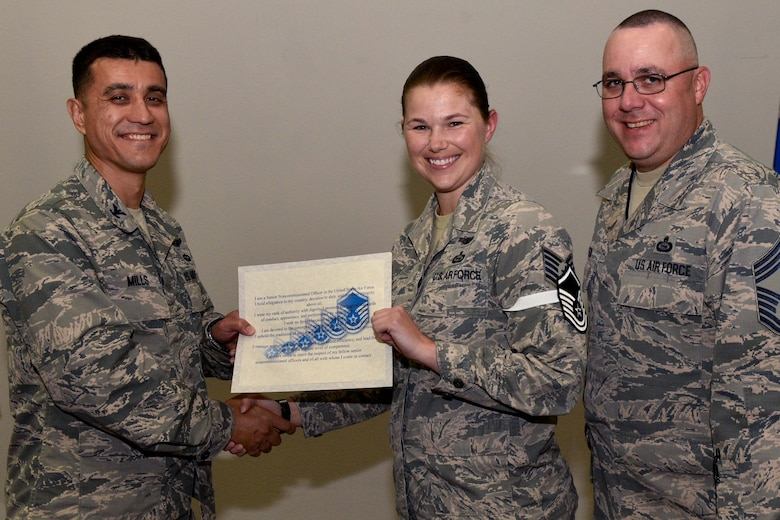 U.S. Air Force Col. Ricky Mills, 17th Training Wing commander, presents Tech. Sgt. Jessica Whitney, 316th Training Squadron instructor, their certificate of selection with Chief Master Sgt. Daniel Stein, 17th TRW command chief, during a Master Sergeant release party at the Event Center on Goodfellow Air Force Base, Texas, May 25, 2018. Goodfellow held the party to notify the selected promotees and to give fellow wingmen and friends an opportunity to congratulate them on their success. (U.S. Air Force photo by Senior Airman Randall Moose)