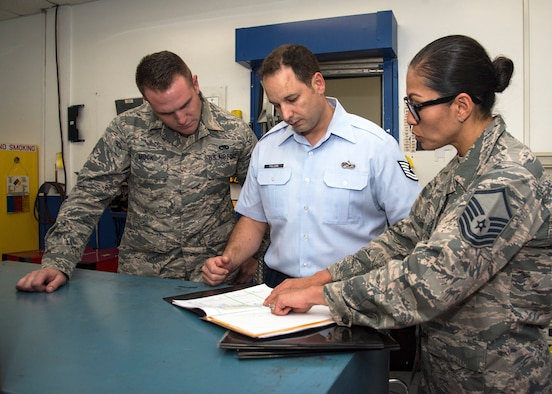U.S. Air Force Master Sgt. Mandy Thorpe, right, lead inspection planner assigned to the 6th Air Mobility Wing Inspector General office, reviews 6th Maintenance Squadron (MXS) unit type codes with Tech. Sgt. Patrick Polcari, center, 6th MXS unit deployment manager and Senior Airman Jean-Paul Mock, 6th MXS aircraft structural journeyman, left, during a Horizontal Inspection at MacDill Air Force Base, Fla., April 30, 2018. This inspection is a wing-level program that verifies the readiness of multiple units.