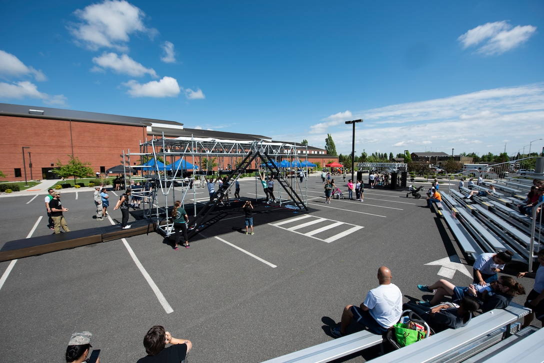 Spectators watch as participants practice training on the obstacles on the Alpha Warrior Battle Rig May 24, 2018 at Fairchild Air Force Base, Wash. The Battle Rig is 10 feet wide, 15 feet tall, 30 feet long and consists of eight obstacles to test participants strength and endurance mentally and physically. (U.S. Air National Guard photo by Staff Sgt. Rose M. Lust)