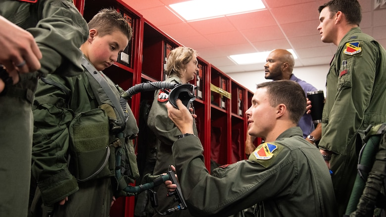 "1st Lt. Matthew Brown shows Cole Lucas aircrew flight equipment May 24, 2018, at Hill Air Force Base, Utah. Eight children and their parents from Make-A-Wish Utah visited Hill for the ""Pilot for a Day"" program. The children toured the base, visited with pilots and ""flew"" in an F-35A cockpit trainer during the event. (U.S. Air Force photo by R. Nial Bradshaw)"