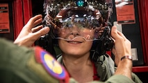 """Micheal Kay tries on a pilot's F-35A helmet, May 24, 2018, at Hill Air Force Base, Utah. Eight children and their parents from Make-A-Wish Utah visited Hill for the """"Pilot for a Day"""" program. The children toured the base, visited with pilots and """"flew"""" in an F-35A cockpit trainer during the event. (U.S. Air Force photo by R. Nial Bradshaw)"""
