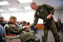 """Col. Jason Rueschoff coins Michelle McConnell, May 24, 2018, at Hill Air Force Base, Utah. Eight children and their parents from the Make-A-Wish Foundation visited Hill for the """"Pilot for a Day"""" program. The children toured the base, visited with pilots and """"flew"""" in an F-35A cockpit trainer during the event. (U.S. Air Force photo by R. Nial Bradshaw)"""