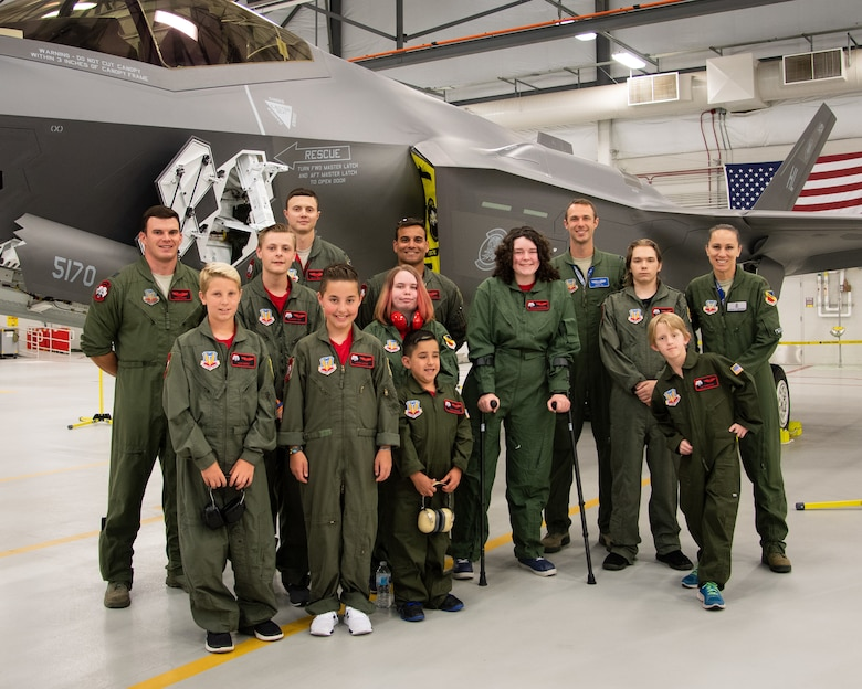 "Children from Make-A-Wish Utah pose for a photo with F35A pilots, May 24, 2018, at Hill Air Force Base, Utah. Eight children and their parents from the Make-A-Wish visited Hill for the ""Pilot for a Day"" program. The children toured the base, visited with pilots and ""flew"" in an F-35A cockpit trainer during the event. (U.S. Air Force photo by R. Nial Bradshaw)"