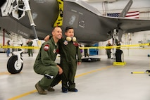 """Dash Garcia poses for a photo with 1st Lt. John Horn, May 24, 2108, at Hill Air Force Base, Utah. Eight children and their parents from Make-A-Wish Utah visited Hill for the """"Pilot for a Day"""" program. The children toured the base, visited with pilots and """"flew"""" in an F-35A cockpit trainer during the event. (U.S. Air Force photo by R. Nial Bradshaw)"""