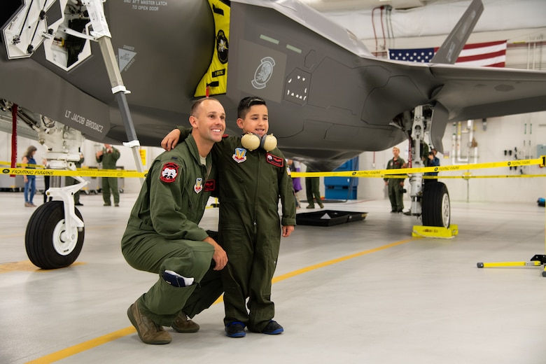 "Dash Garcia poses for a photo with 1st Lt. John Horn, May 24, 2108, at Hill Air Force Base, Utah. Eight children and their parents from Make-A-Wish Utah visited Hill for the ""Pilot for a Day"" program. The children toured the base, visited with pilots and ""flew"" in an F-35A cockpit trainer during the event. (U.S. Air Force photo by R. Nial Bradshaw)"