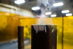 Smoke rises from a welded piece of metal in the metals fabrication shop on Joint Base Elmendorf-Richardson, Alaska, May 9, 2018. Aircraft Metals Technology Airmen measure broken or worn parts, draw working sketches, make templates, perform precision grinding remove poisonous or corrosive deposits from parts, and write programs for machines using manual and computer-aided manufacturing.