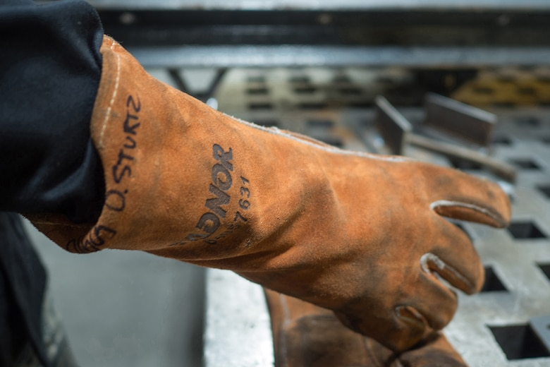 Airman Dalton Sturtz, a native of Seguin, Texas, an aircraft metals technology journeyman assigned to the 3rd Maintenance Squadron, takes off his protective gloves after welding a metal plate in the metals fabrication shop on Joint Base Elmendorf-Richardson, Alaska, May 9, 2018. Aircraft Metals Technology Airmen measure broken or worn parts, draw working sketches, make templates, perform precision grinding remove poisonous or corrosive deposits from parts, and write programs for machines using manual and computer-aided manufacturing.
