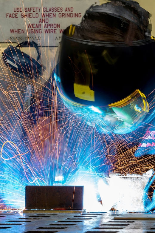 Airman Dalton Sturtz, a native of Seguin, Texas, an aircraft metals technology journeyman assigned to the 3rd Maintenance Squadron, practices welding a metal plate in the metals fabrication shop on Joint Base Elmendorf-Richardson, Alaska, May 9, 2018. Aircraft Metals Technology Airmen measure broken or worn parts, draw working sketches, make templates, perform precision grinding remove poisonous or corrosive deposits from parts, and write programs for machines using manual and computer-aided manufacturing.