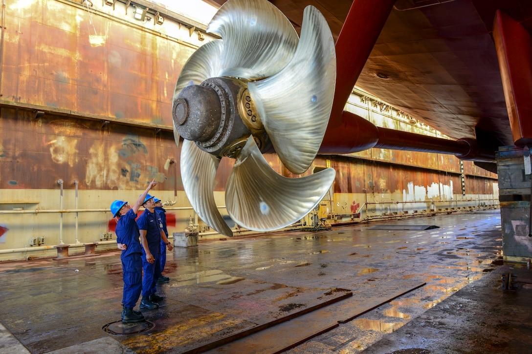 Coast Guard personnel look up at a huge shiny metal propeller.
