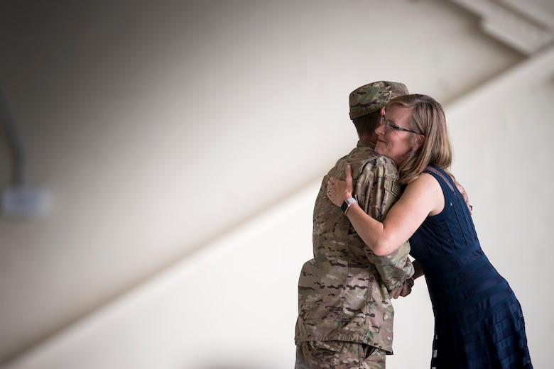 Maj. Gen. Scott Zobrist, 9th Air Force commander, hugs JoAnne Valenzia, wife of Col. Jeffery Valenzia, after presenting her with a coin, May 23, 2018, at Moody Air Force Base, Ga. After relinquishing command Valenzia will assume duties as the executive assistant to the North American Aerospace Defense Command/U.S. Northern Command commander at Peterson Air Force Base, Colo. (U.S. Air Force photo by Staff Sgt. Ryan Callaghan)
