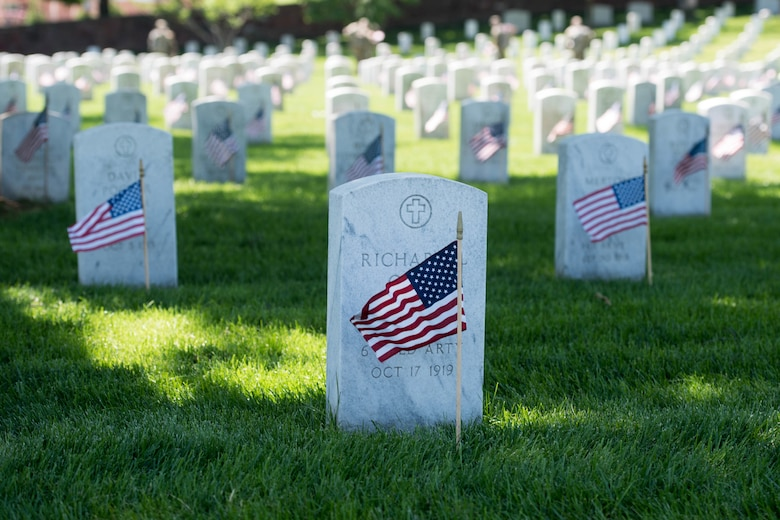 Flags placed in front of headstone at Arlington National Cemetery.