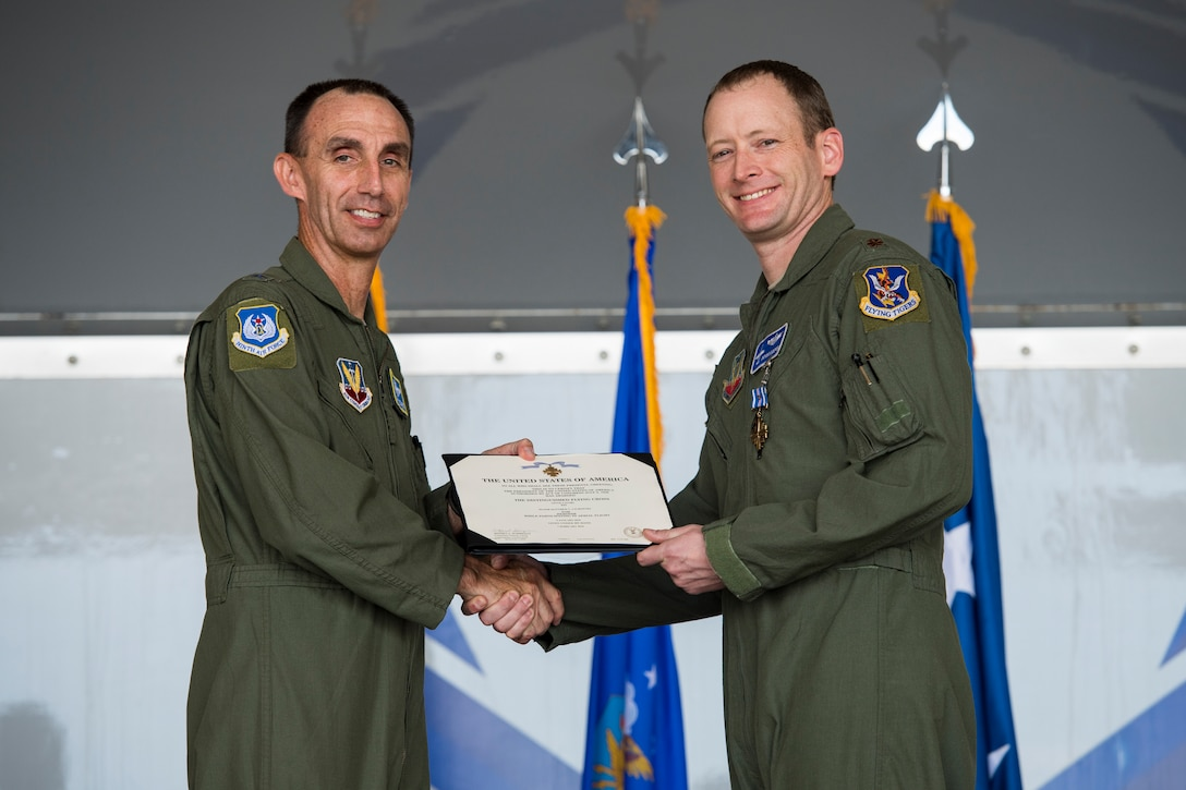 "U.S. Air Force Maj. Gen. Scott J. Zobrist, left, 9th Air Force commander, presents Maj. Matthew ""Chowder""' Cichowski, 74th Fighter Squadron A-10C Thunderbolt II pilot, with a Distinguished Flying Cross with valor during an award ceremony, May 23, 2018, at Moody Air Force Base, Ga. Cichowski and his wingman were outnumbered 3-to-1 Jan. 9, 2018, when providing close-air-support for ground forces. Through his efforts, Cichowski identified 25 enemy fighters and employed a 2,000 pound Joint Direct Attack Munition to thwart the enemy. (U.S. Air Force photo by Senior Airman Janiqua P. Robinson)"