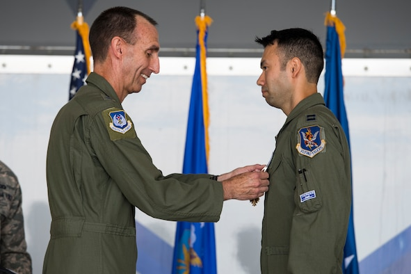 "U.S. Air Force Maj. Gen. Scott Zobrist, left, 9th Air Force commander, places a Distinguished Flying Cross medal on Capt. William ""Archer"" Dana, 74th Fighter Squadron A-10C Thunderbolt II pilot, during an award ceremony, May 23, 2018, at Moody Air Force Base, Ga. Dana, along with his wingman, was alerted Aug. 14, 2017, by a Joint Terminal Attack Controller the enemy had breached friend lines in eight locations. In a three-hour period, Dana employed 11,000 pounds of ordnance and destroyed 10 enemy defensive fighting positions. (U.S. Air Force photo by Senior Airman Janiqua P. Robinson)"