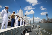 U.S. Marines and Sailors 'man the rails' aboard San Antonio-class amphibious transport dock USS Arlington during the parade of ships commencing Fleet Week New York, May 23, 2018. Marines, Sailors, and Coast Guardsmen are in New York to interact with the public, demonstrate capabilities and teach the people of New York about America's sea services.
