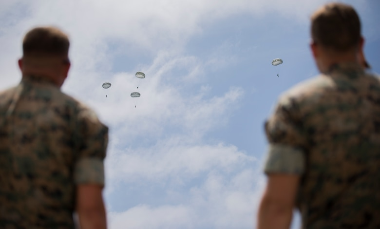 Marines with 3rd Air Delivery Platoon, Landing Support Company, 3rd Transportation Support Battalion, 3rd Marine Logistics Group, monitor the jump paths of Marines free-falling from a C-130 May 22, 2018, on Ie Shima, Okinawa, Japan. The Marines conducted air drop operations dropping a type-five platform, door bundles, free fall and static line jumpers, and the Polaris MRZR onto the island. 3rd MLG Marines worked alongside Marines with 3rd Reconnaissance Battalion, 3rd Marine Division, during the regularly scheduled training evolution to complete their first ever successful drop of a Polaris MRZR from a C-130.