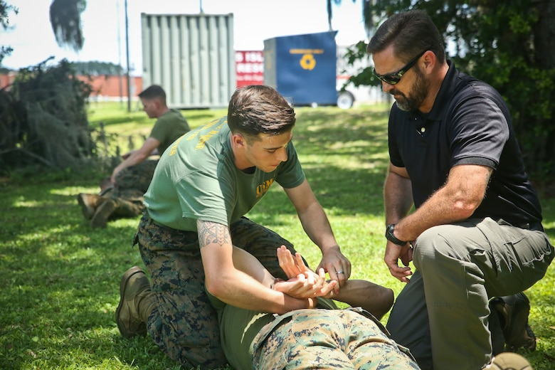 Ron Videtto, right, shows Cpl. Jacob Blea restraining techniques as part of Security Augmentation Force training aboard Marine Corps Recruit Depot Parris Island May 23. SAF is a detail of Marines selected to assist the Provost Marshal's Office with security in emergency situations. Blea is an administrative specialist with Headquarters and Headquarters Squadron and Videtto is with PMO.
