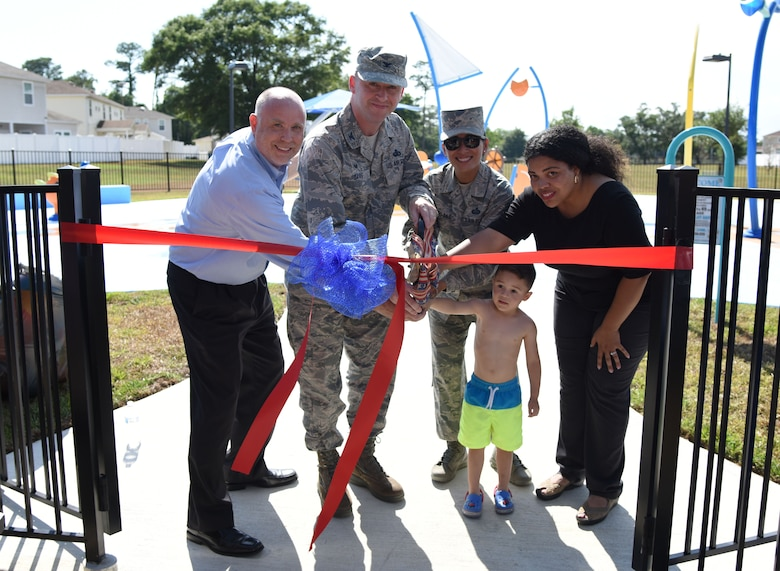 U.S. Air Force Col. Danny Davis, 81st Mission Support Group commander,  helps cut a ribbon during the Splash Pad Ribbon Cutting Ceremony at the West Falcon Housing area in Biloxi, Mississippi, May 22, 2018. The Hunt Company project will provide more recreational activities for all Keesler family housing families. (U.S. Air Force photo by Kemberly Groue)