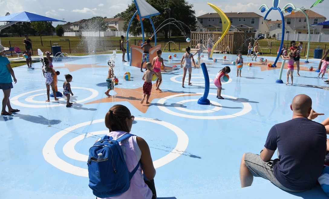 Military children play on the splash pad during the Splash Pad Ribbon Cutting Ceremony at the West Falcon Housing area in Biloxi, Mississippi, May 22, 2018. The Hunt Company project will provide more recreational activities for all Keesler family housing families. (U.S. Air Force photo by Kemberly Groue)