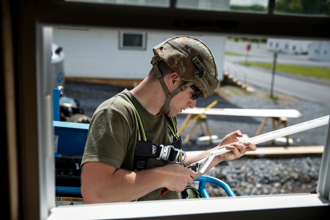 U.S. Marine Lance Cpl. Wyatt Miller, combat engineer with Engineer Company C, 6th Engineer Support Battalion, 4th Marine Logistics Group, cuts a panel of siding for the window frame at a construction site during exercise Red Dagger at Fort Indiantown Gap, Pa., May 23, 2018.
