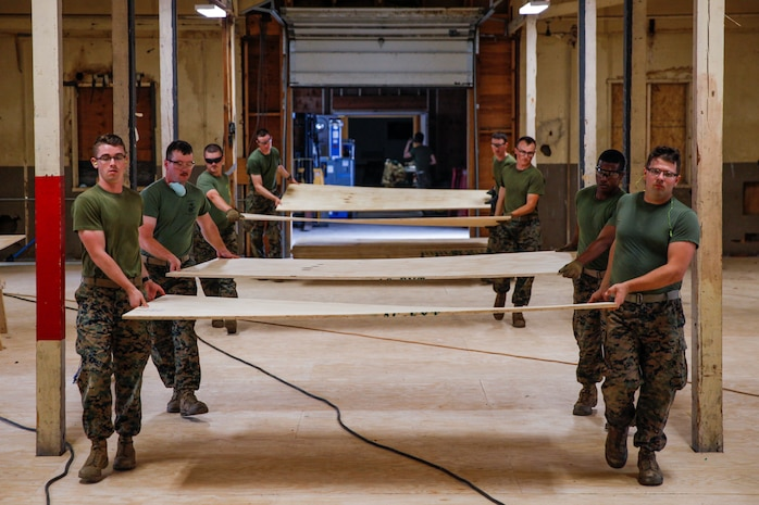 U.S. Marines with 6th Engineer Support Battalion, 4th Marine Logistics Group, carry plywood  at a construction site during exercise Red Dagger at Fort Indiantown Gap, Pa., May 23, 2018.