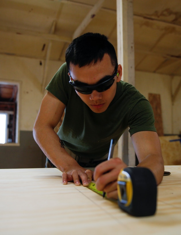U.S. Marine Lance Cpl. Thang Q. Duong, squad leader with Headquarters and Service Company, 6th Engineer Support Battalion, 4th Marine Logistics Group, measures a piece of plywood at a construction site during exercise Red Dagger at Fort Indiantown Gap, Pa., May 23, 2018.