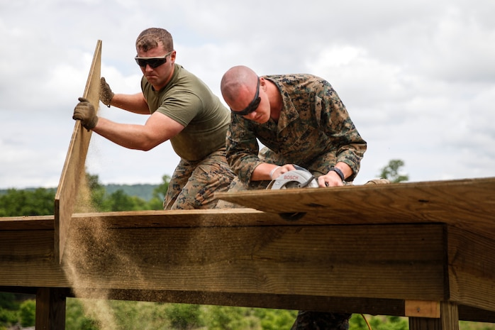U.S. Marines Lance Cpl. Caleb J. Malone (left), combat engineer with Bridge Company C, 6th Engineer Support Battalion, 4th Marine Logistics Group, discards a piece of cut plywood as Lance Cpl. Matthew P. Winter (right), combat engineer with Engineer Company C, 6th ESB, 4th MLG, cuts plywood with a circular saw at a construction site during exercise Red Dagger at Fort Indiantown Gap, Pa., May 23, 2018.