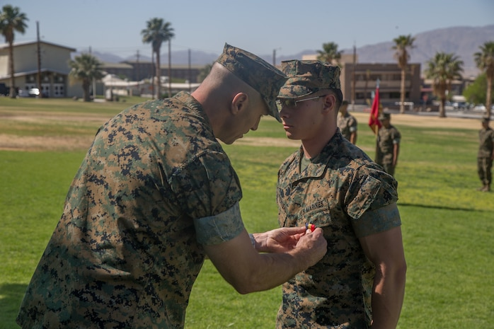Lt. Col. John S. Kinitz, commanding officer, 3rd Light Armored Reconnaissance Battalion, awards Lance Cpl. Tucker Watson-Veal, scout, 3rd LAR the Navy and Marine Corps Medal during a ceremony at Lance Cpl. Torrey L. Gray Field aboard the Marine Corps Air Ground Combat Center, Twentynine Palms, Calif., May 24, 2018. Watson-Veal was awarded the Navy and Marine Corps Medal after rescuing a drowning person from rapid currents while on leave in 2016. (U.S. Marine Corps photo by Lance Cpl. Preston L. Morris)
