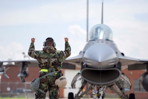 An Airman with the 180th Fighter Wing maintenance group uses hand signals to direct an F-16 Fighting Falcon during a training exercise on May 19, 2018. Airmen wore Mission-Oriented Personal Protective gear while maintaining, launching and recovering aircraft to simulate operating in an environment in which a chemical attack occurred.