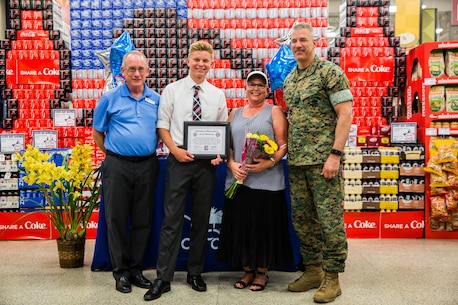 Maj. Gen. William F. Mullen III, commanding general, Marine Corps Air Ground Combat Center, presents Cameron Lay, a student at Yucca Valley High School, with a college scholarship from Fisher House Foundation at the Commissary aboard the Combat Center, Twentynine Palms, Calif., May 17, 2018. Defense Commissary Agency partnered with Fisher House, an organization that focuses on administering scholarships for military children, to award Lay for his outstanding, academic achievements and service to the community. (U.S. Marine Corps photo by Lance Cpl. Margaret Gale)