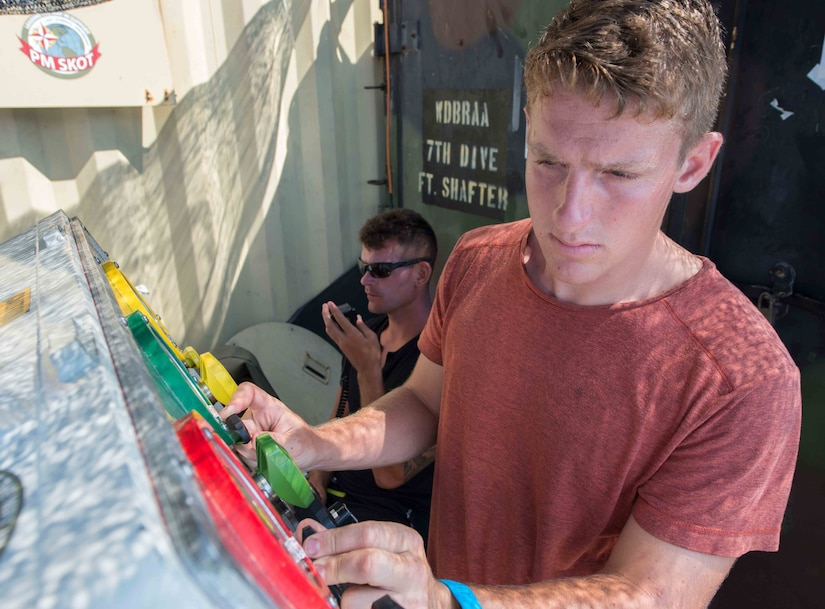Army Spc. Timothy Sparks, a diver with the 7th Engineer Dive Detachment, monitors the air levels of two divers during an underwater recovery mission near Nha Trang, Vietnam.