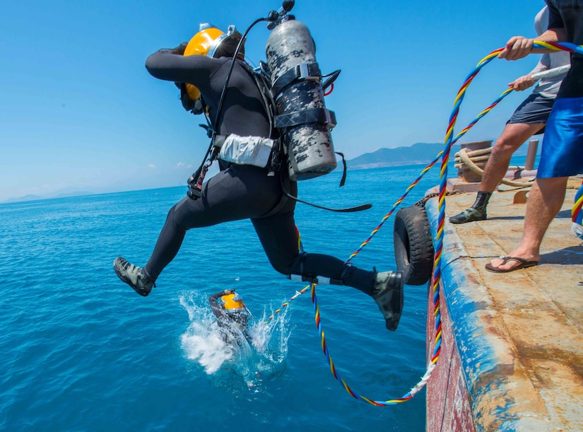 Army divers from the 7th Engineer Dive Detachment jump into the water during an underwater recovery mission near Nha Trang, Vietnam.