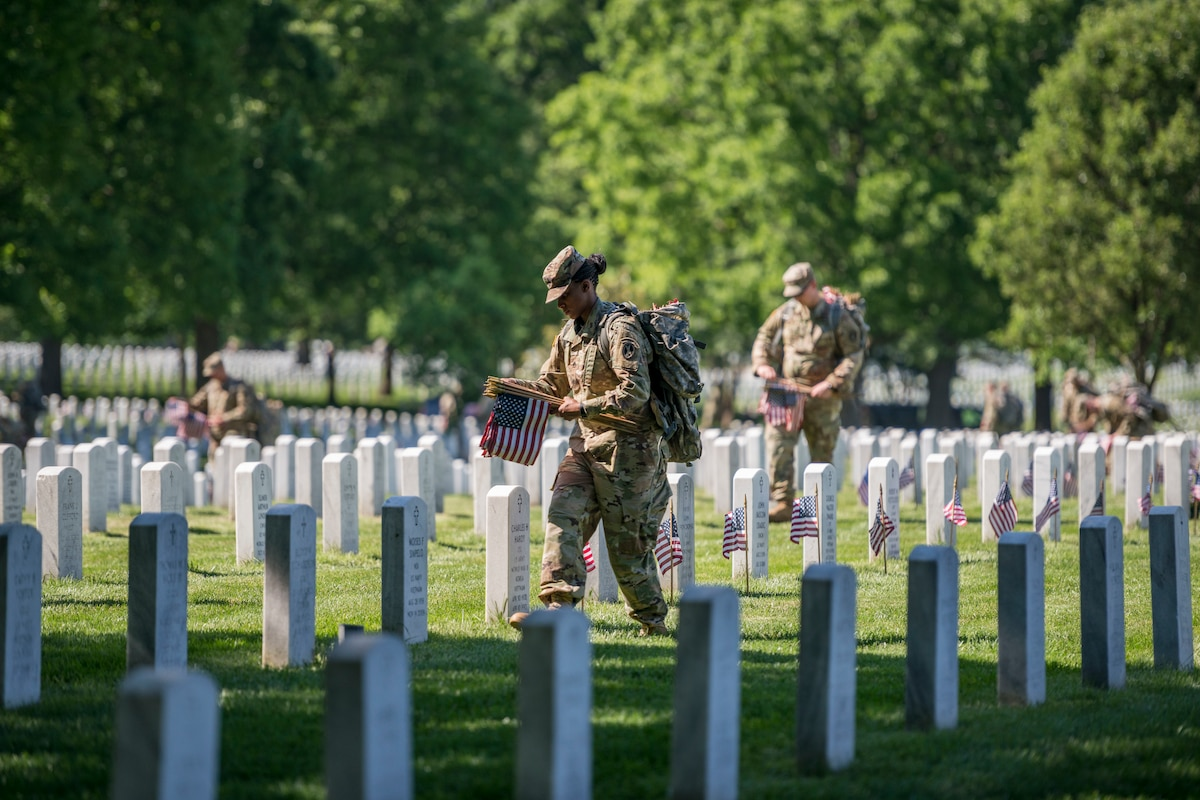 Soldiers place American flags in front of headstones.