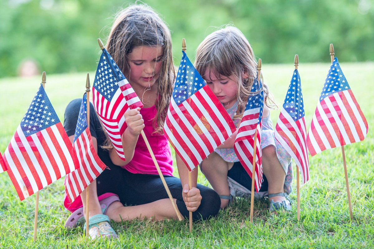 Two young girls place American flags in the ground.