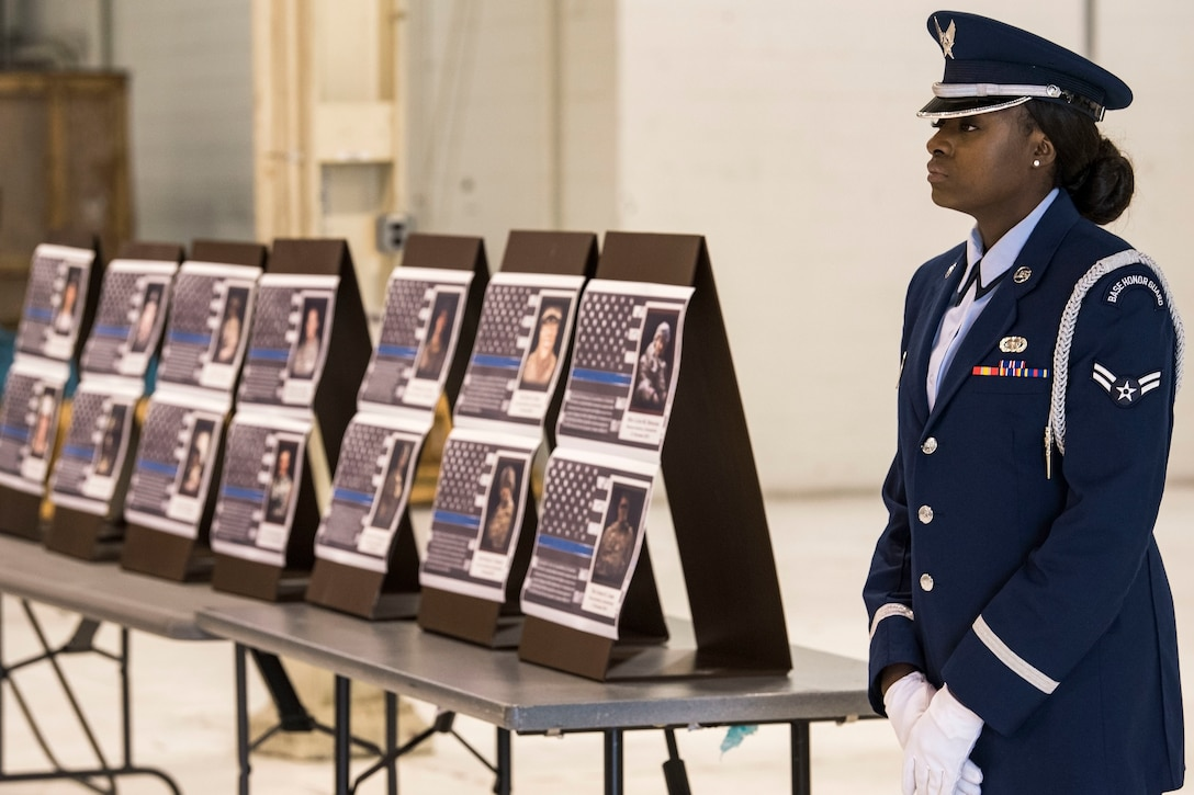 An airman stands beside 14 placards in a room.