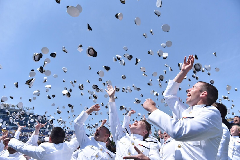 U.S. Naval Academy midshipmen from the Class of 2018 toss their hats in the air during the graduation and commissioning ceremony at Navy/Marine Corps Memorial Stadium in Annapolis, Md.