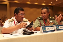 Malaysian Navy Rear Adm. Khairul Anuar Yahya, left, assistant chief of staff for operations and exercise, Naval Headquarters and and Brig. Gen. Tengku Muhammad Fauzi Tengku Ibrahim, Commander 10th Brigade, speak during the Pacific Amphibious Leaders Symposium (PALS) in Honolulu, Hawaii, May 21-24, 2018.