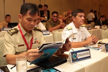 Singapore Armed Forces Lt. Col. Alex Ho, Liasion Officer to the U.S. Marine Corps, flips through the Pacific Amphibious Leaders Symposium (PALS) photo book during PALS in Honolulu, Hawaii, May 23, 2018.