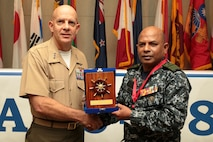 U.S. Marine Corps Lt. Gen. David H. Berger, commander, U.S. Marine Corps Forces, Pacific, left, receives a gift from Rear Adm. Udeni Indranatha Serasinghe, Director General Land Operation and Director, Sri Lanka Navy Infantry and Navy Marine, at the close of the Pacific Amphibious Leaders Symposium (PALS) in Honolulu, Hawaii, May 24, 2018.