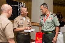 Philippine Marine Corps Maj. Gen. Alvin A. Parreno, center, commandant, Philippine Marine Corps, receives a gift from Malaysian Brig. Gen. Tengku Muhammad Fauzi Tengku Ibrahim, right, commander, 10th Brigade, during the Pacific Amphibious Leaders Symposium (PALS) 2018 in Honolulu, Hawaii, May 24, 2018.
