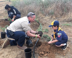 A Cub Scout and his leader help plant native vegetation near the Santa Ana River during a May 12 planting event in Norco, California.